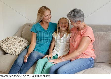 Senior caucasian grandmother on couch smiling with adult daughter and granddaughter. happy three generation family spending time together at home.