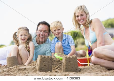Families On Beach Making Sand Castles Smiling