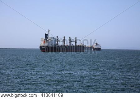 March 20, 2021 Long Beach, California - USA: Container Ships wait their turn to be unloaded of their shipping containers in the port of long beach california. Editorial Use Only.