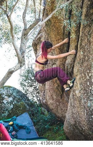 Bouldering On Natural Terrain, A Strong Woman Climbs A Boulder, A Girl Goes In For Sports In Nature,