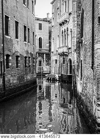Black and white beautiful water reflections in the small canal, Venice, Italy