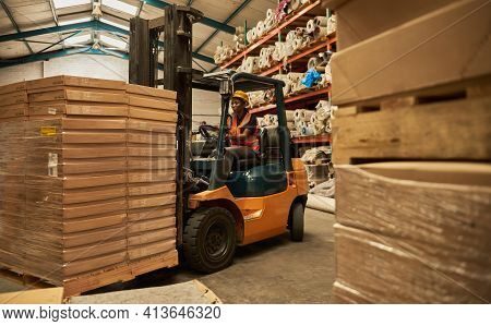 African Female Forklift Operator Moving Stock Around A Warehouse