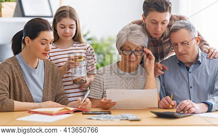 Family are sitting at a desk with a paper receipt and calculating expenses, managing budget.