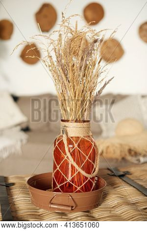 Bouquet Of Dried Flowers In Orange Vase On Table In Home Cozy Interior Of Room. Scandinavian Design.