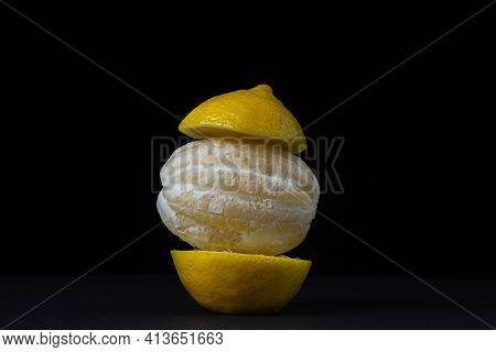 Lemon On A Dark Background. Peeled Lemon On A Black Background. Creative Photo Of Lemon.