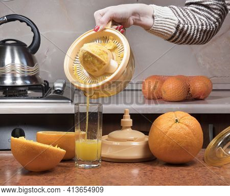 Female Hand Pouring Orange Juice Into Glass. Closeup On Women's Hand Making Fresh Orange Juice.