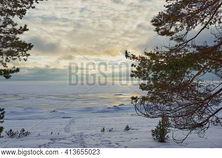 Evening Winter Landscape Of A Large Frozen Lake Or Bay With A Horizon Line And Cloudy Sky
