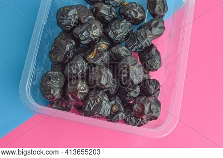 Fresh Dates Over Blue And Pink Background. Dates Are The Fruit Of The Date Palm Tree Which Is Grown