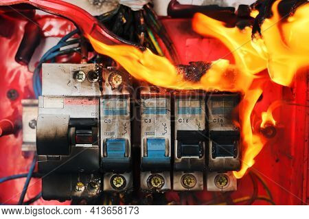 Burning Switchboard From Overload Or Short Circuit On Wall Close-up. Circuit Breakers On Fire From O