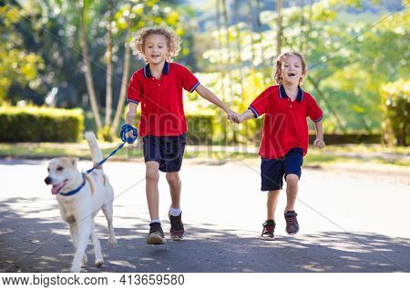 Child Walking Dog. Kid Playing With Cute Puppy. Little Boy Running With His Pet. Children Play In Su