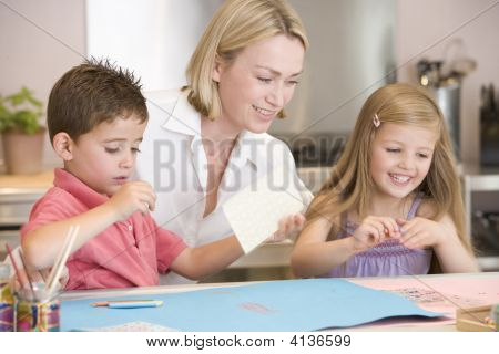 Woman And Two Young Children In Kitchen With Art Project Smiling