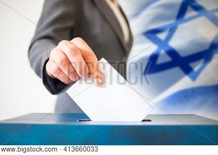 elections in Israel. Hand of a woman putting her vote in the ballot box. Waved Israel flag on background.