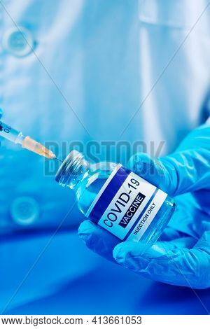 closeup of a healthcare or laboratory worker, wearing blue surgical gloves, filling a syringe from a vial of a simulated covid-19 vaccine