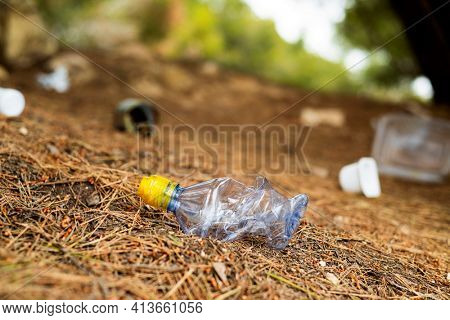 closeup of a used plastic bottle thrown on the ground of a forest, next to some other garbage, such as used food cans and plastic containers