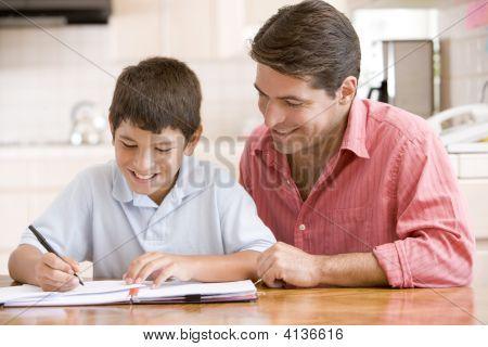 helfen jungen in Küche Hausaufgaben und lächelnd mann