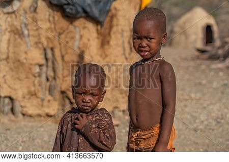 Khorixas. Namibia, January 13. 2020: Himba Tribe Boys Stay And Looking To The Camera At The Himba Vi