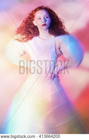 Sophisticated female model with lush red curly hair posing in a white art dress. A studio portrait with mixed red color lighting in haze. Fashion art.