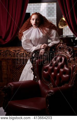 Portrait of a s sophisticated lady with lush red hair with fine curls standing in a vintage interior in art dress with a ruffled renaissance collar. History of fashion and hairstyles.