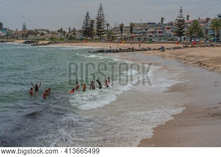 Swakopmund, Namibia - Jan 11, 2020: Public Beach With A Group Of People Swimming In The Ocean At The