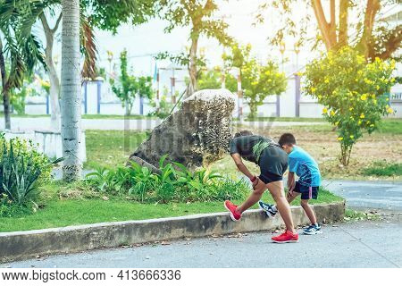 Back View Of Sportive Happy Mother Training Her Son Doing Stretching Before Exercise In Garden. Athl