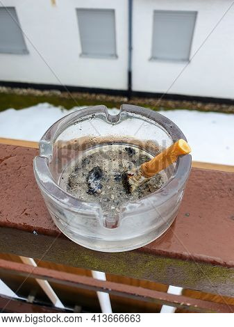 A Stubbed Out Cigarette In An Ashtray Outside On The Balcony. Stop Smoking.