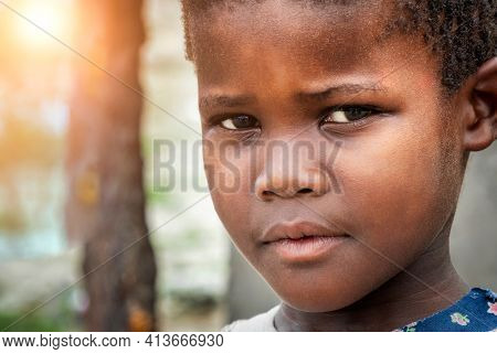 Small African girl standing in the yard in a village in Africa