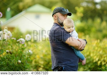 Little Baby Boy In His Fathers Arms. Dad And Son Having Fun On Sunny Summer Day In City Park. Adorab