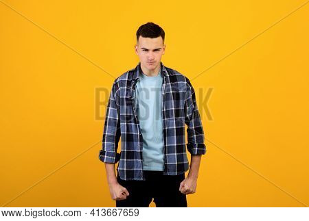 Enraged Millennial Man Clenching His Fists, Trying To Suppress His Anger On Orange Background. Human