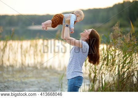 Little Baby Boy In His Mothers Arms. Mom And Son Having Fun On Sunny Summer Day In City Park. Adorab