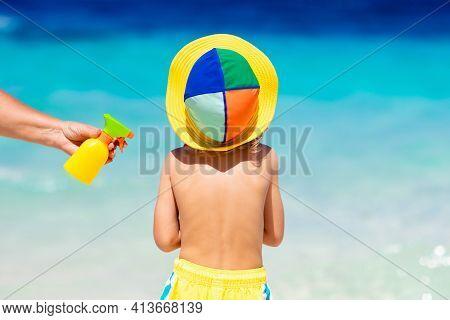 Mom Applying Sunscreen On Child. Safe Beach Fun.