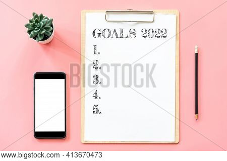 2022 New Year Concept. Goals List In Stationery, Blank Clipboard, Smartphone, Pot Plant On Pink Past