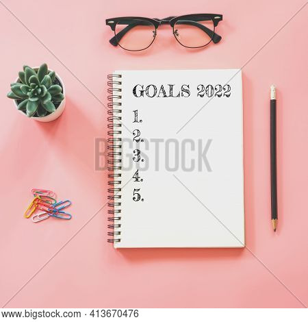 2022 New Year Concept. Goals List In Notepad, Smartphone, Stationery On Pink Pastel Color With Copy