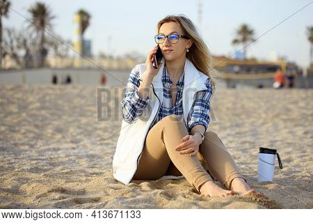 Young Blond Woman At The Beach Talking With Mobile Phone. Portrait Of Cheerful Woman With Glasses An