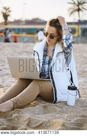 Freelance Woman Working In Vacation With Laptop On The Beach. Woman With Sunglasses Winter Beach. Em