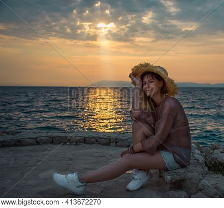 Woman Resting By The Sea In The Evening And Enjoying The Sunset