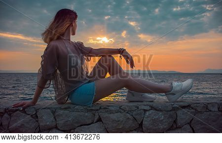 Woman Sits On Stones By The Sea And Looks At The Sunset