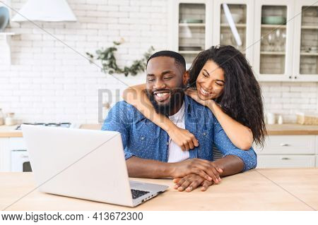 Cute Multiracial Couple Enjoys Leisure Time At Home With A Laptop, Happy Woman And Man In Embrace Lo