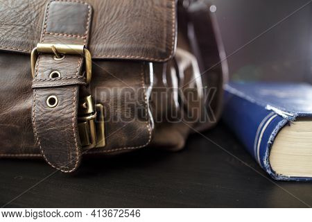 Old Leather Briefcase With Metal Buckles And A Closed Book Lying On The Table. Education Concept.