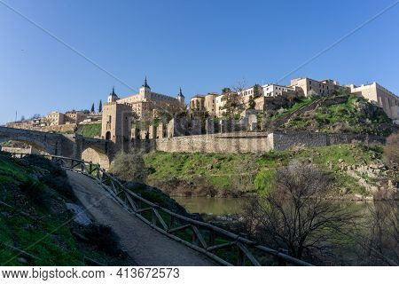 A View Of The Historic Spanish City Of Toledo On The Tagus River With The Roman Bridge In The Foregr