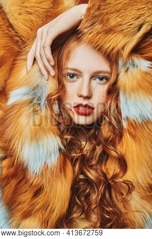 Fur coat fashion. Portrait of a beautiful young woman with long red hair posing in a luxurious fox fur coat.