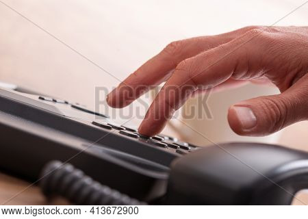 Low Angle Closeup View Of A Male Finger Dialing Telephone Number Using Black Landline Phone.