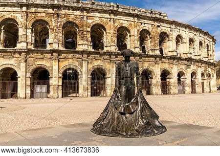 Nimes, France - 15 March, 2021: View Of The Roman Amphitheater In Nimes With The Statue Of The Bullf