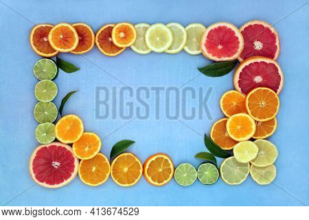 Citrus fruit for good health background border high in antioxidants and vitamin c.  Also high in anthocyanins, lycopene and dietary fibre. Health care and summer sunshine concept. On mottled blue.