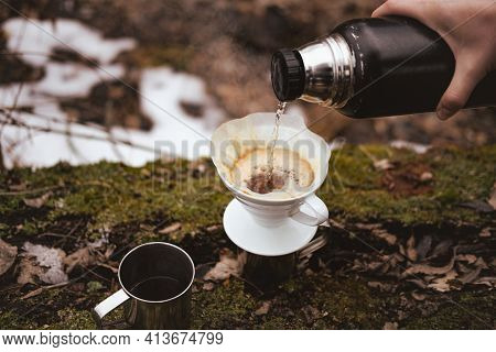 Brewing Pour Over Coffee In Nature At A Hiking Trip. Hand Pouring Hot Steaming Water Into A Paper Fi