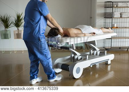 Long Shot Of A Relaxed Bare-backed Young Woman Enjoying Body Massage Done By Professional Masseur Or