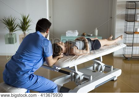 Rear View Of A Professional Masseur In Blue Uniform, Holding Woman's Head, Who Is Lying Down On A St