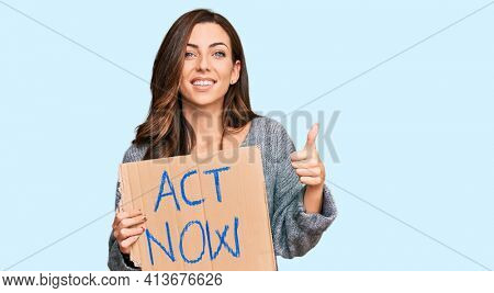 Young brunette woman holding act now banner smiling happy and positive, thumb up doing excellent and approval sign