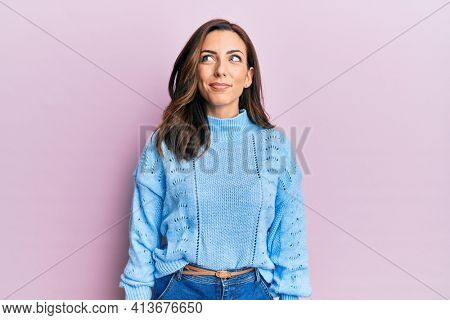 Young brunette woman wearing casual winter sweater over pink background smiling looking to the side and staring away thinking.