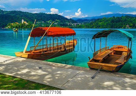 Famous Traditional Wooden Pletna Boat Moored At The Pier. Rowing Pletna Boat On The Lake Bled And Pi