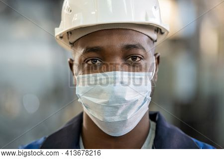 Young factory worker of African ethnicity in workwear, hardhat and protective mask looking at you while standing in front of camera